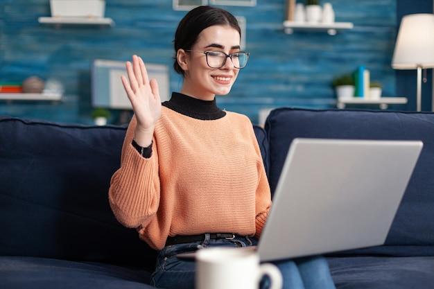 Jonge vrouw begroet haar leraar tijdens een virtuele videogesprekvergadering over een universitair project. student in woonkamer op online internetwebvideoconferentie tijdens virtuele e-learningklas
