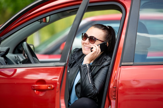 Jonge vrouw bellen door gsm, smartphone op de parkeerplaats van de auto, transport concept