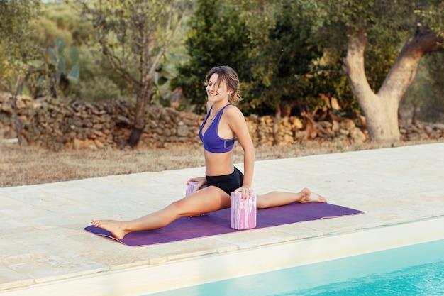 Jonge vrouw beoefenen front splits pose in de buurt van een zwembad