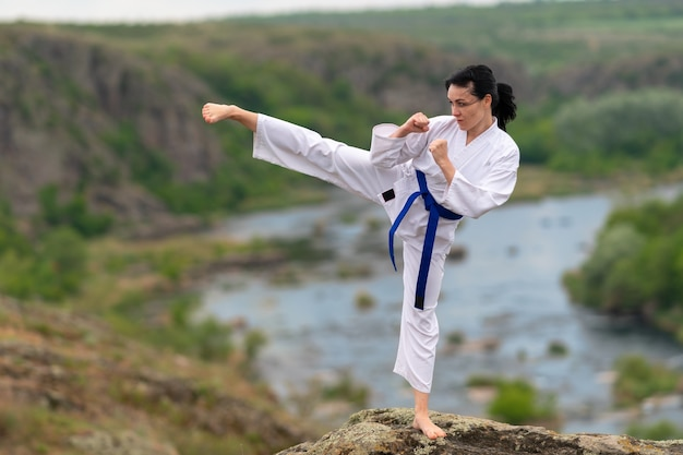Jonge vrouw beoefenen van kickboksen buiten in de natuur balanceren