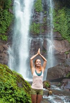 Jonge vrouw beoefenen van yoga bij de waterval