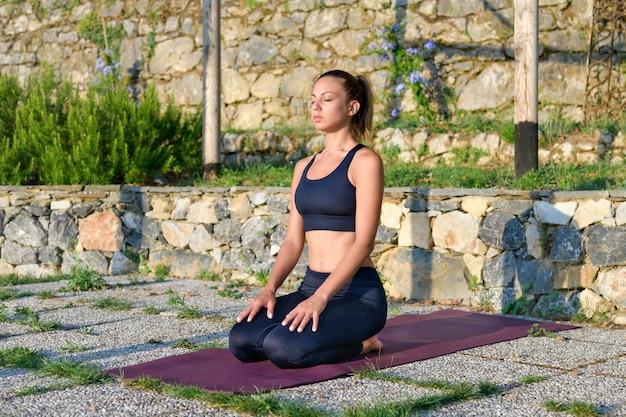 Jonge vrouw beoefenen van yoga buiten mediteren op een stenen terras