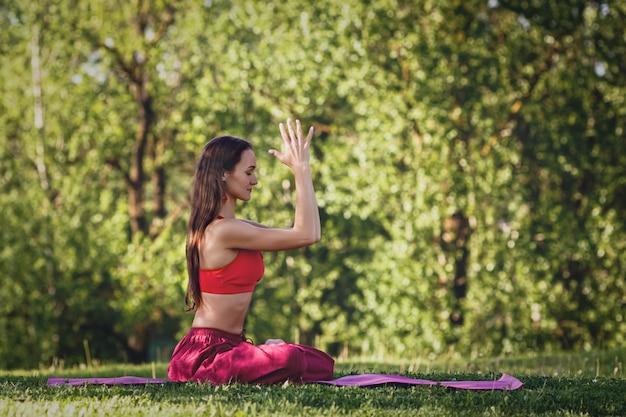 Jonge vrouw beoefenen van yoga buitenshuis. het wijfje mediteert openlucht in het park van de de zomerstad.