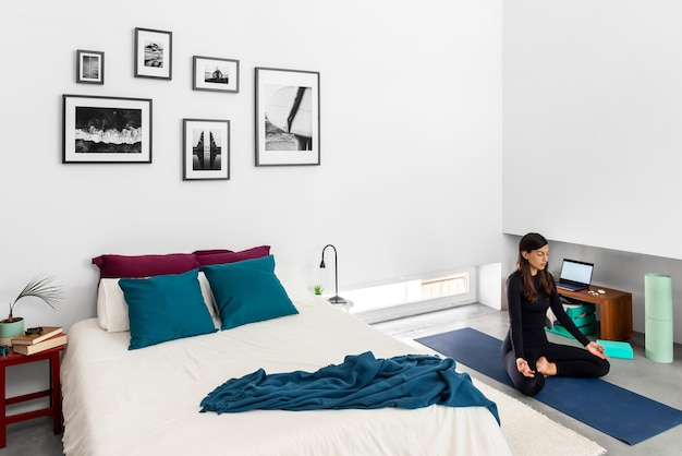 Jonge vrouw beoefenen van yoga en meditatie in lotus houding in slaapkamer met interieur in minimalistische stijl