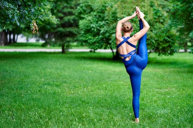 Jonge vrouw beoefenen van yoga in het park