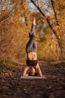 Jonge vrouw beoefenen van yoga oefening in herfst park met gele bladeren