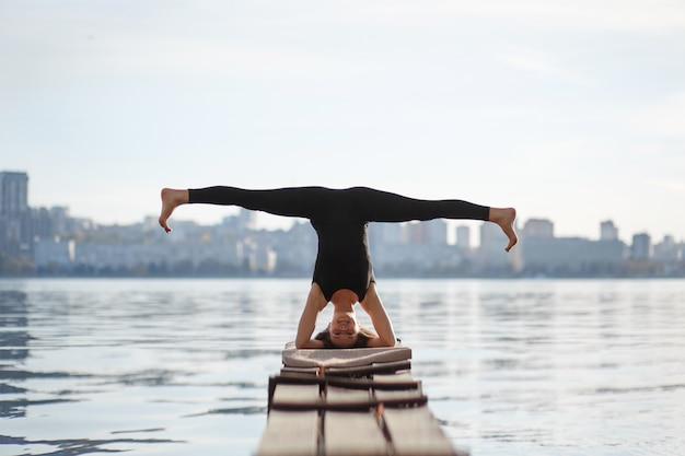 Jonge vrouw beoefenen van yoga oefening op rustige houten pier met stad sport en recreatie in de stad haast