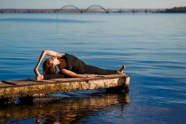 Jonge vrouw beoefenen van yoga oefening op rustige houten pier met stad. sport en recreatie in de stad