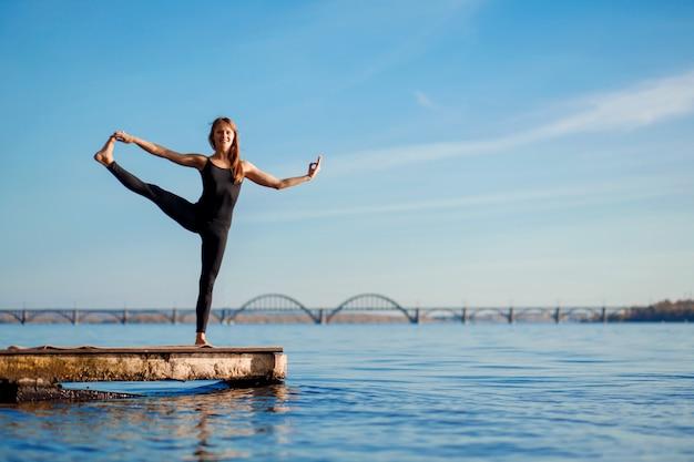 Jonge vrouw beoefenen van yoga oefening op rustige houten pier met stad