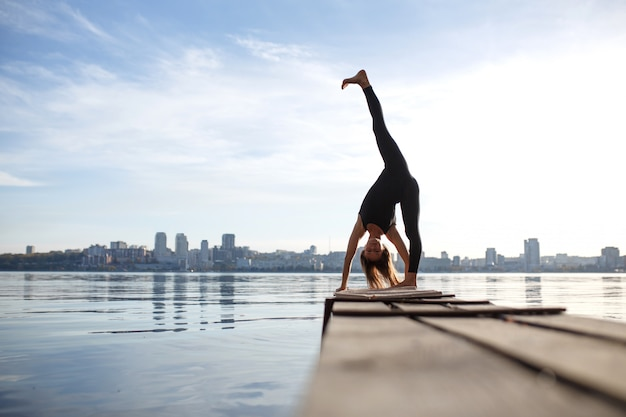Jonge vrouw beoefenen van yoga oefening op rustige houten pier