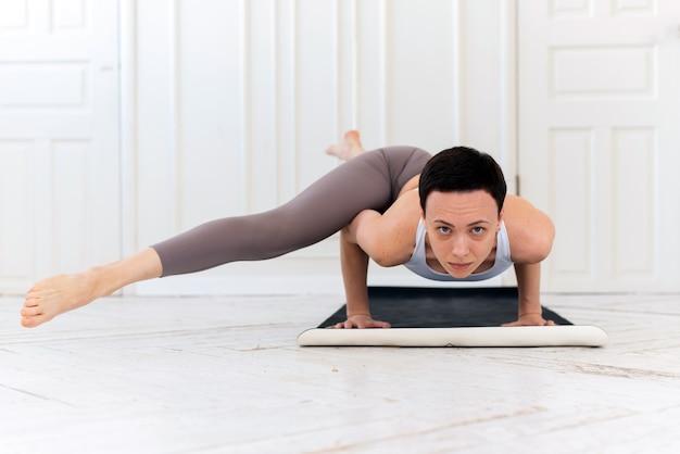 Jonge vrouw beoefenen van yoga op een lichte achtergrond. gezond levensstijlconcept.