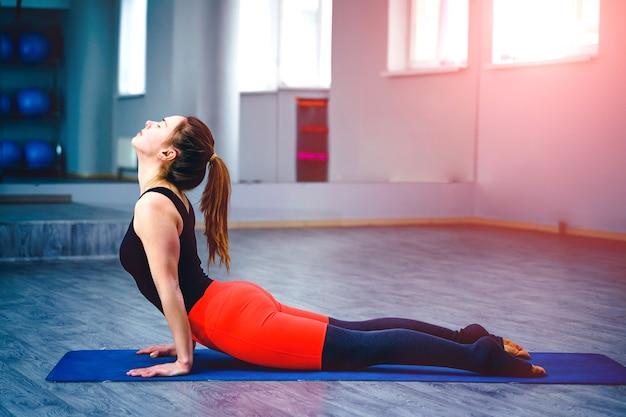 Jonge vrouw beoefenen van yoga-positie in een overdekte sportschool studio. concept van een gezonde levensstijl.