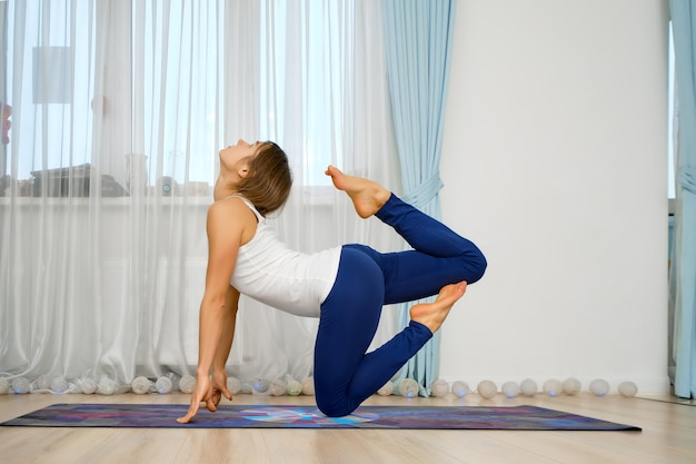Jonge vrouw beoefenen van yoga thuis, staat in eenbenige koningsduif pose