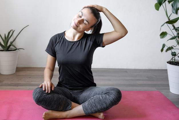 Jonge vrouw beoefent asana's thuis op de mat, yoga thuis, de spieren van het lichaam strekkend.