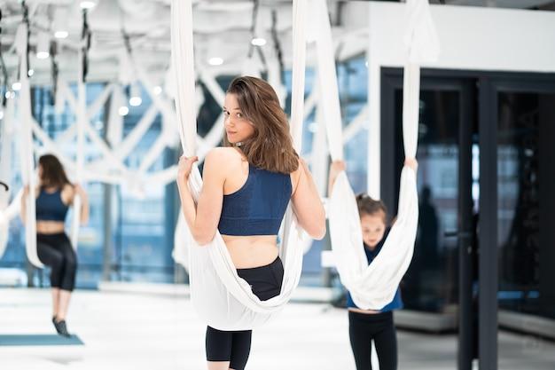 Jonge vrouw beoefent luchtfoto anti-zwaartekracht yoga
