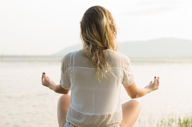 Jonge vrouw beoefent yoga en mediteert in de lotushouding op het strand, met uitzicht op het water. geweldig concept van meditatie en ontspanning.