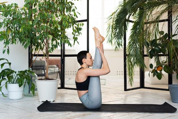 Jonge vrouw beoefent yoga in een kamer met planten.