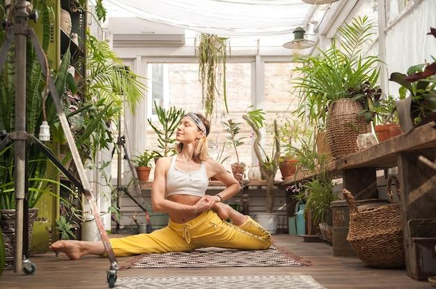 Jonge vrouw beoefent yoga thuis onder bloemen. stedelijke jungle en gymnastiek, yoga, pilates.