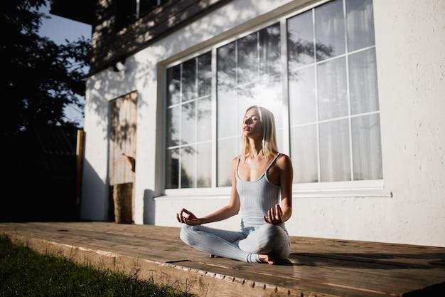Jonge vrouw beoefent yoga zittend in de lotuspositie op een houten podium in de tuin met haar handen op de knieën in de zonnige ochtend