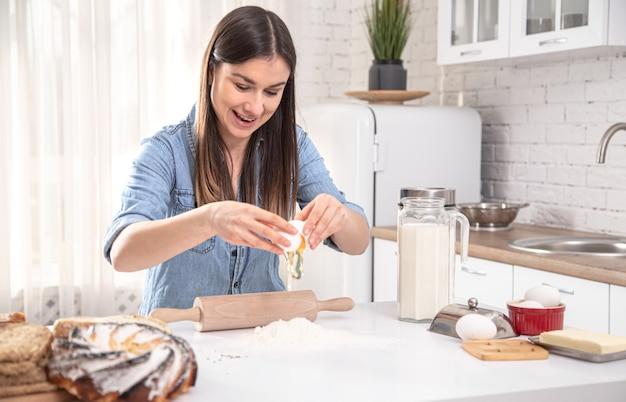 Jonge vrouw bereiden zelfgemaakte taarten in de ruime lichte keuken.