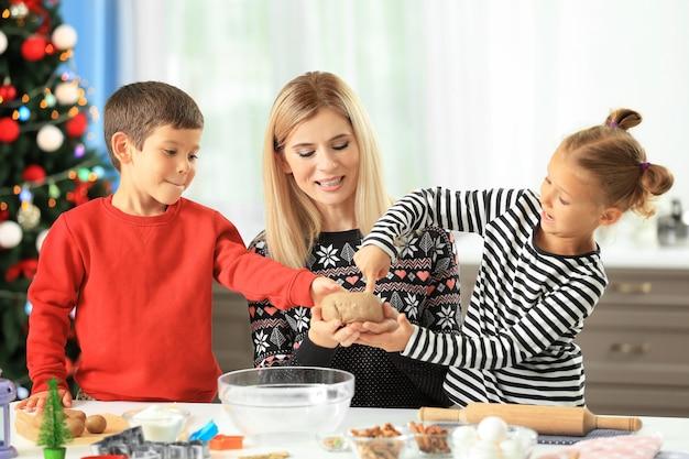 Jonge vrouw bereidt kerstkoekjes met kleine kinderen in de keuken