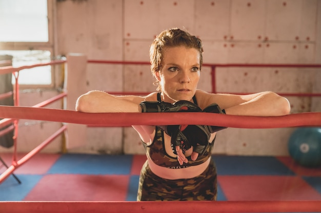 Jonge vrouw bereidt zich voor op wedstrijden mma in de kooi. training in een sporthal