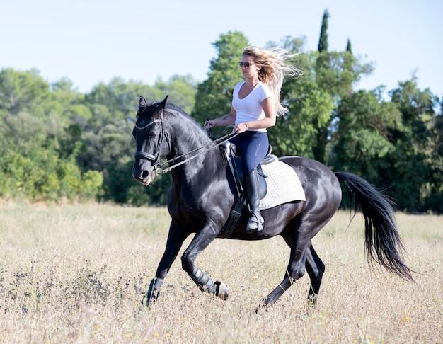 Jonge vrouw berijden van een paard in de natuur