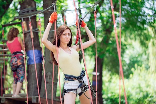 Jonge vrouw besteden hun vrije tijd in een touwenparcours. vrouw die zich bezighouden met touwpark.