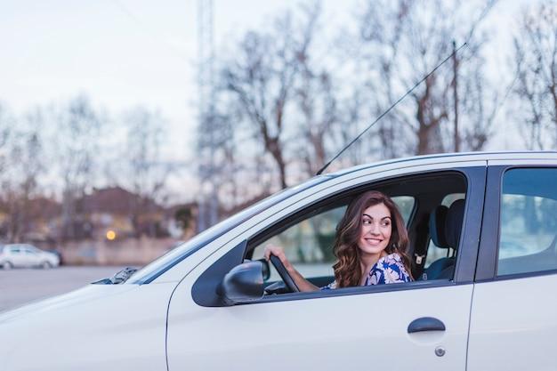Jonge vrouw besturen van een auto in de stad. portret van een mooie vrouw in een auto, kijkt uit het raam en glimlacht. reizen en vakanties concepten