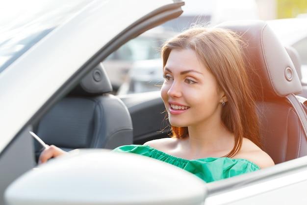 Jonge vrouw besturen van een auto in de stad