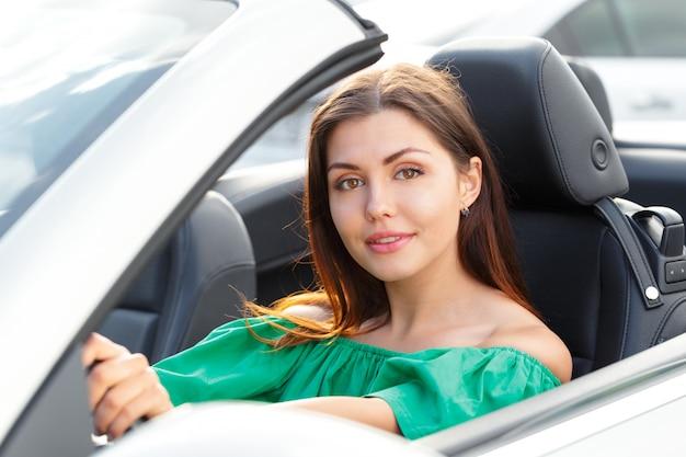 Jonge vrouw besturen van een auto in de stad.