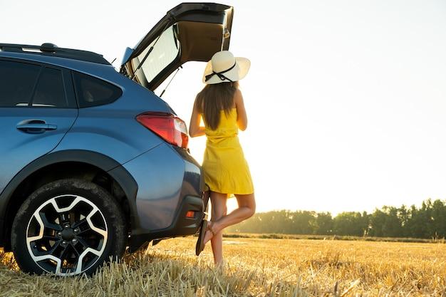 Jonge vrouw bestuurder in gele zomerjurk en strooien hoed staande in de buurt van een blauwe auto genieten van warme zomerdag bij zonsondergang.