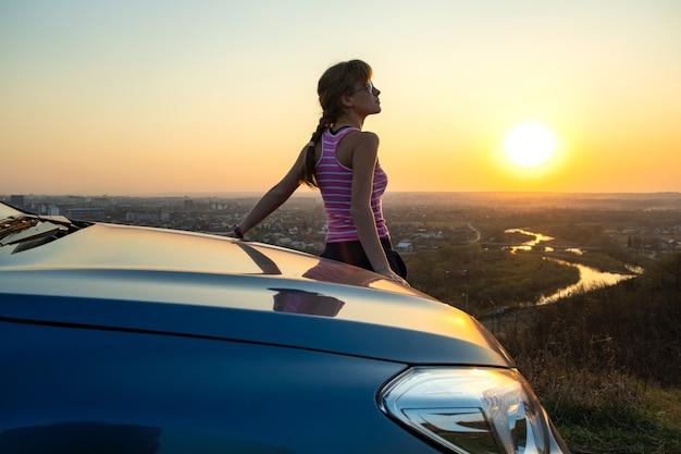 Jonge vrouw bestuurder permanent in de buurt van haar auto genieten van warme zonsondergang. meisje reiziger leunend op de motorkap van het voertuig kijken naar de horizon van de avond.