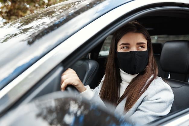 Jonge vrouw bestuurder zitten in de auto, rijden naar het werk in een gezichtsmasker