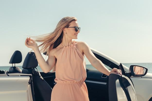 Jonge vrouw bestuurt een auto op het strand
