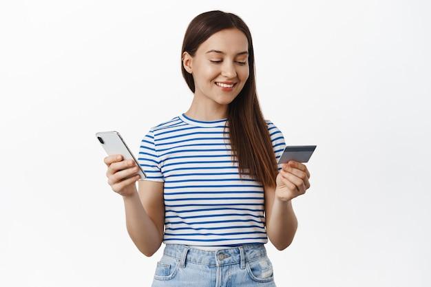 Jonge vrouw betaalt met creditcard en mobiele telefoon, lacht en ziet er ontspannen uit, koopt iets in de internetwinkel, koopt een smartphone-applicatie, staat over een witte muur.