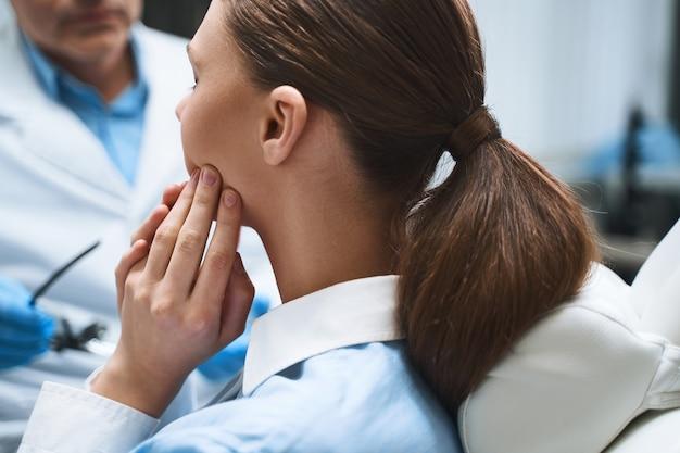 Jonge vrouw bezoekt mannelijke tandarts in modern kantoor vanwege gebitsproblemen