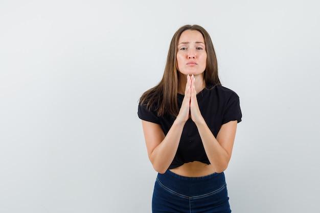 Jonge vrouw bidden gebaar in zwarte blouse doen en op zoek verdrietig.