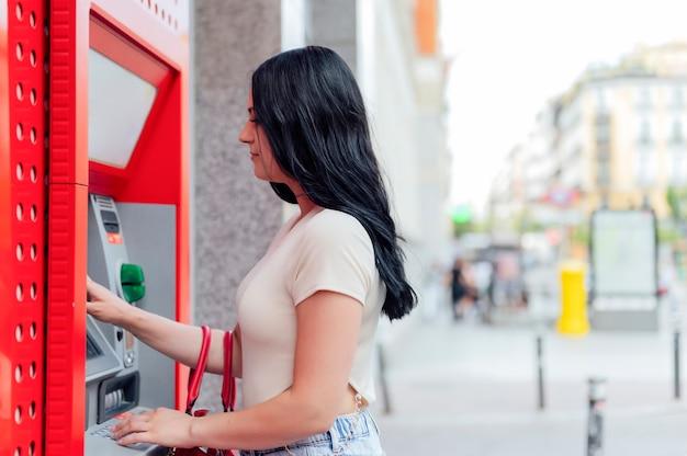 Jonge vrouw bij de geldautomaat