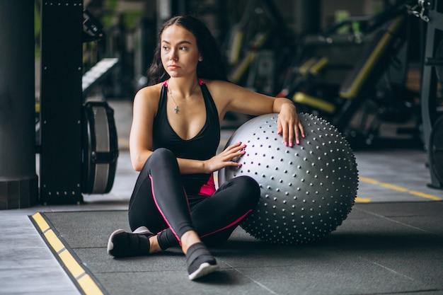 Jonge vrouw bij de gymnastiek die met apparatuur uitoefent