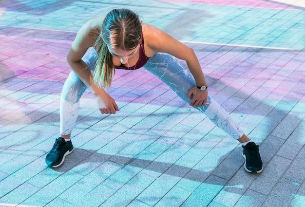 Jonge vrouw bij de gymnastiek die uitrekkende oefeningen doen