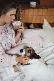 Jonge vrouw bij de open haard drinken cacao met marshmello met hond.
