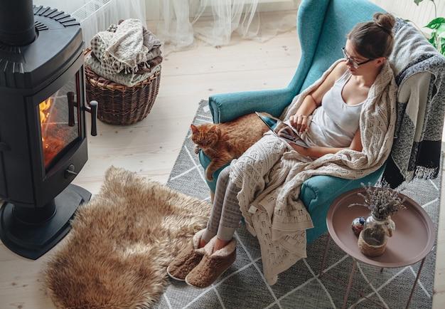 Jonge vrouw bij de open haard, zittend in een gezellige fauteuil, met een warme deken, met behulp van een tablet