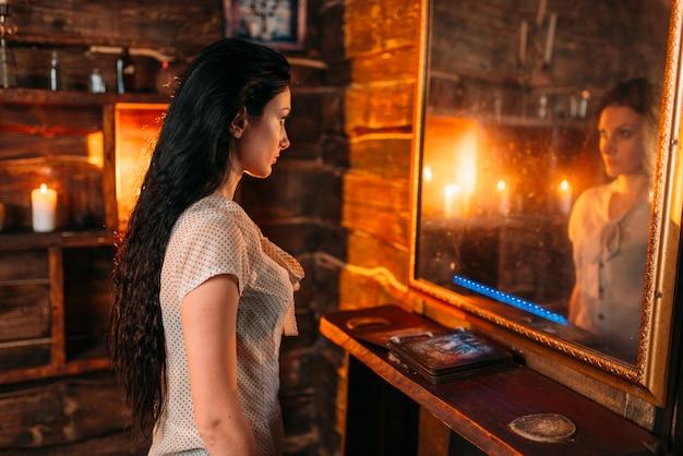 Jonge vrouw bij de spiegel op spirituele seance, hekserij. vrouwelijke voorspeller noemt de geesten magie