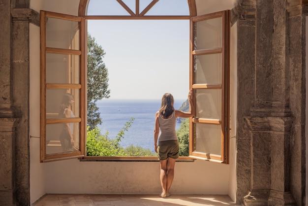 Jonge vrouw bij een groot open raam.