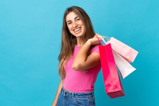 Jonge vrouw bij geïsoleerde blauwe holding het winkelen zakken en het glimlachen