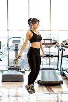 Jonge vrouw bij gymnastiek opleiding met touwtjespringen