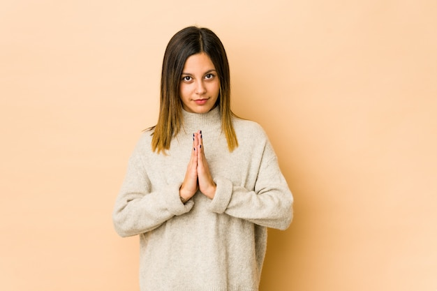 Jonge vrouw bij het beige muur bidden, die toewijding tonen