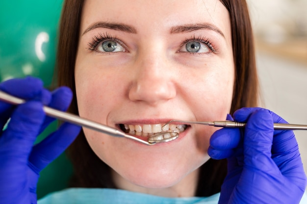 Jonge vrouw bij het tandartsoverleg. controle en tandheelkundige behandeling in een tandheelkundige kliniek. mondhygiëne en behandeling.