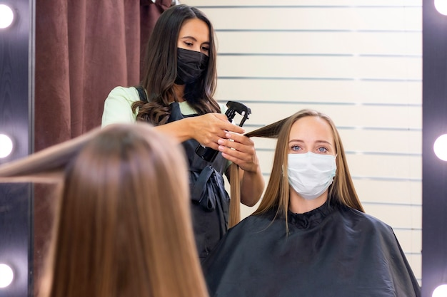 Jonge vrouw bij kapper die beschermend masker draagt als gevolg van een pandemie van het coronavirus
